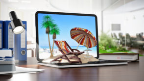 Umbrella, sunbed and plam trees on sand standing on notebook computer. Online travel destinations booking concept